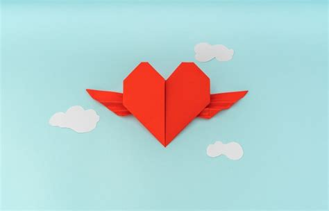Red paper origami heart with wings and cloud on blue