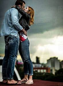 a, couple, standing, and, kissing, on, a, city, rooftop