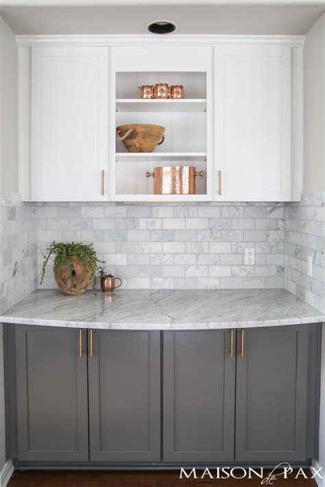 toned gray  white cabinets marble subway tile