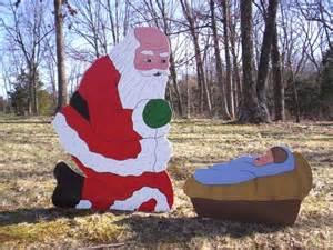 santa praising kneeling praying before manger crib with baby