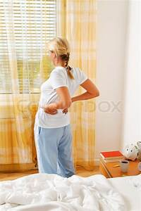 a woman has the morning after waking up pain stock With back pain after waking up