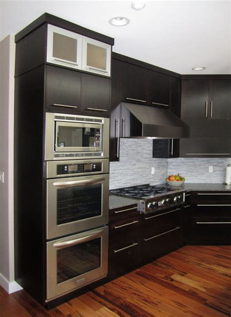 View of the double wall ovens, built in microwave, gas cooktop, and hood..