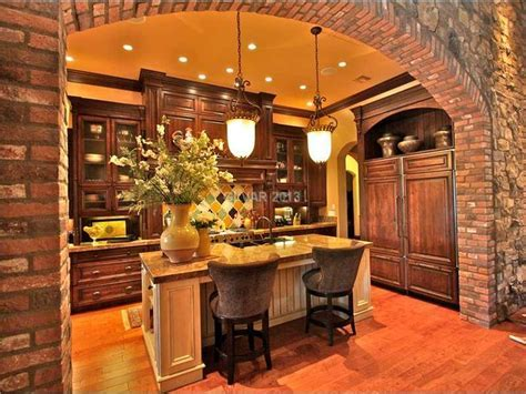 Tuscan kitchen with pendant lights and stone arch. The