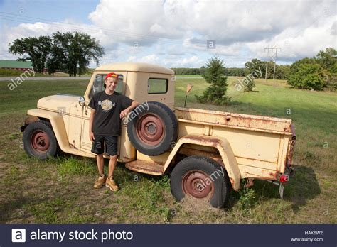 young teen standing   vintage willys jeep pickup truck  stock photo royalty