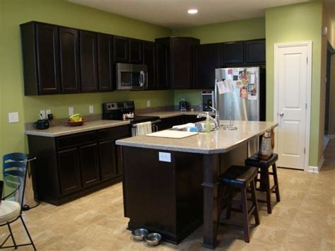 Kitchen dark cabinets, light counters, green walls
