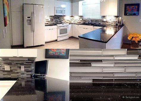 kitchen with glass backsplash white kitchen cabinets black galaxy countertop gray glass
