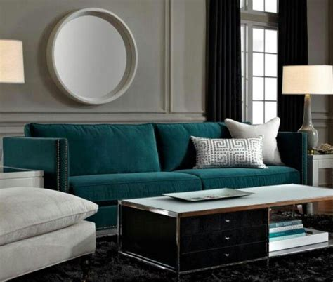 teal sofa is a gem against grey walls a rug and midnight curtains decorating with