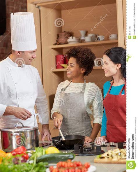 le chef cuisine les femmes et le chef heureux font cuire la cuisson dans