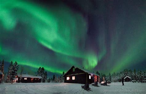 Aurora borealis over a cabin near Kiruna, Sweden ...