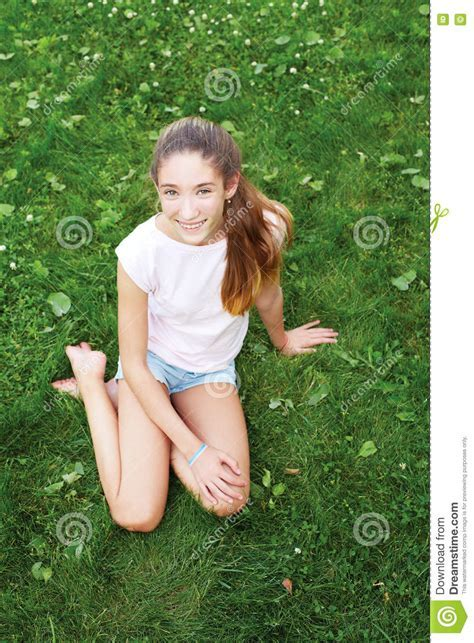 Cute Teen Girl Sitting On The Grass In The Park Stock