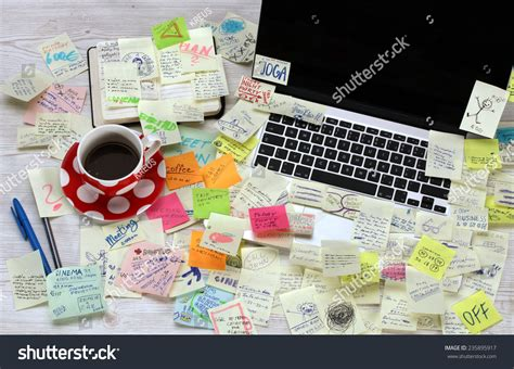 bureau post it office desk with laptop covered by post it papers stock