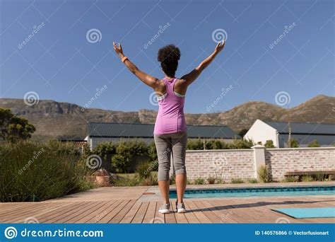 Woman Performing Yoga In The Backyard Of Home Stock Photo
