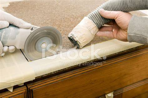 workers cutting sink in a granite countertop stock
