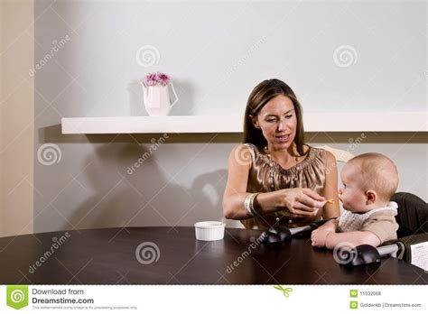 feeding baby sitting in high chair royalty free