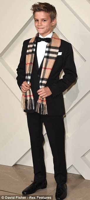 romeo beckham steals the spotlight from his parents at launch of burberry s festive caign