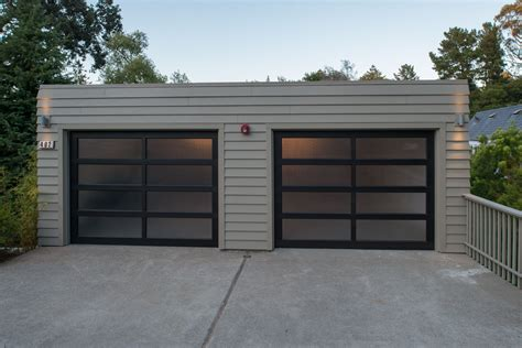 A Contemporary Garage With Beige Siding And A Black Framed