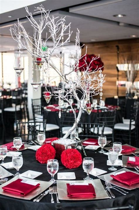 picture of a black and wedding tablescape with silver touches and a whitewashed tree with