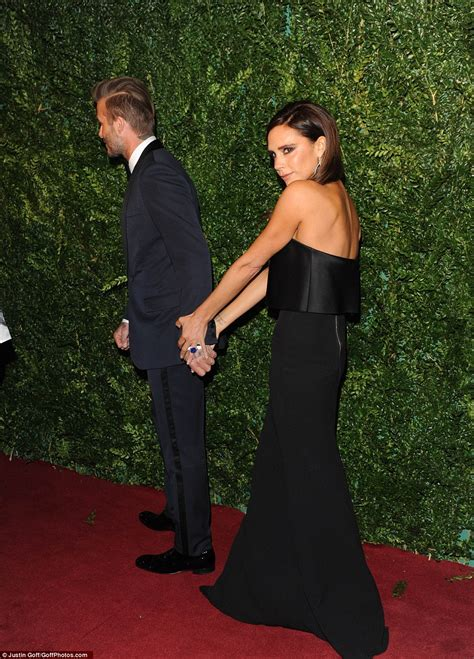 David Beckham holds wife Victoria's hand at the Evening ...
