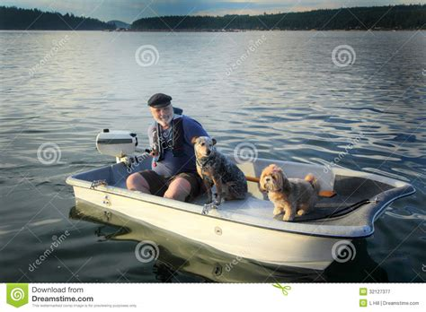 Dog Boat Captain Hat by Boater With Dogs On Small Boat Royalty Free Stock