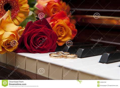 wedding rings   piano keyboard  flowers stock image