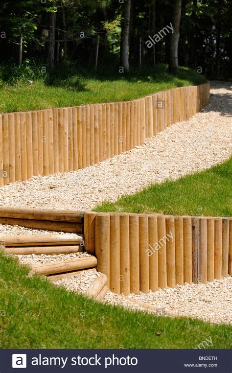 wood post retaining wall gravel pathway with wooden fence posts used as a retaining wall uk stock photo royalty free