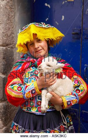 Andean Girl Wearing Traditional Clothes With An Alpaca