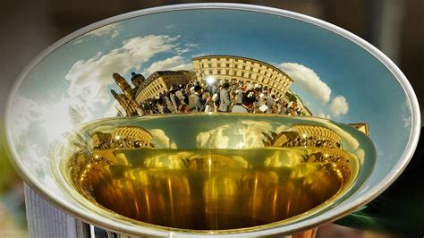 A marching band is reflected in the bell of a horn during