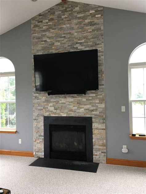 stacked stone floor  vaulted ceiling wall  natural gas fire place   television