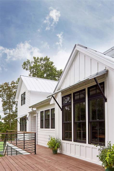 white vertical exterior siding black trim windows window awnings dark wood decking metal
