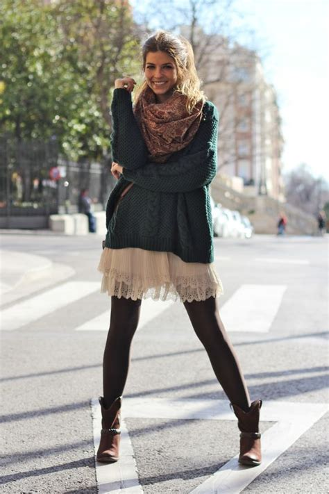 Picture Of a white lace dress a dark green oversized sweater a scarf black tights and brown boots