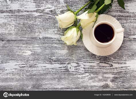 live wood coffee table coffee cup and white flowers on wooden table
