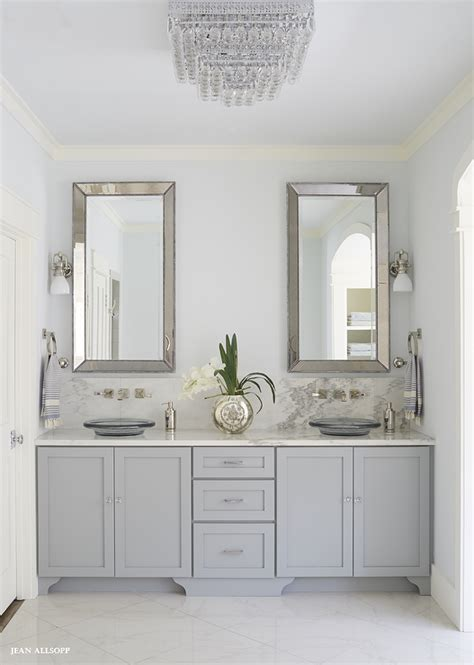 fabulous gray bathroom features  gray dual vanity adorned  glass knobs paired