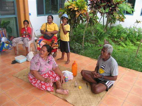 Palau People sitting down front of their house and eating ...