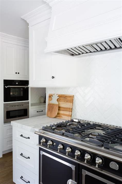white vent hood  black range transitional kitchen