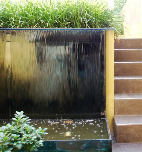 water feature for wall garden with glass water wall and polished concrete steps simon scott landscaping