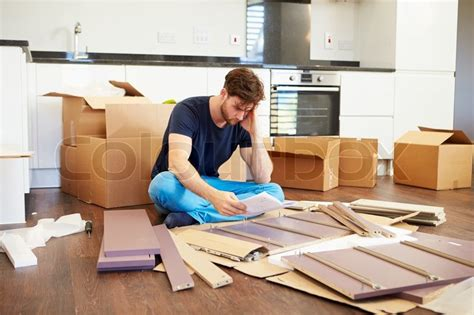 self assembly furniture frustrated man putting together self assembly furniture stock photo colourbox