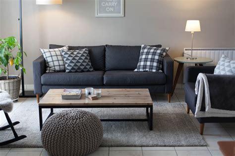 canapé gris foncé mur gris clair et canapé gris foncé coussins graphiques