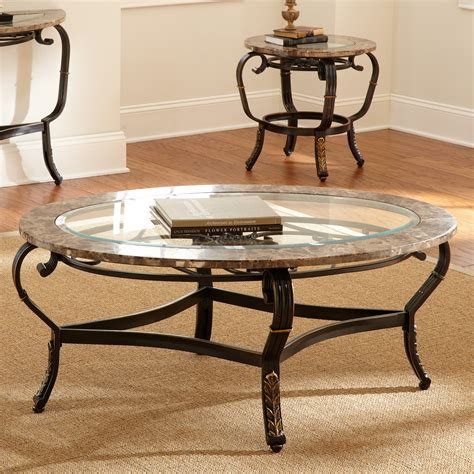 This coffee table's beveled glass tabletop is surrounded by a metal frame, which showcases decorative post legs and a geometrically detailed stretcher make it unmistakably glam. Steve Silver Gallinari Oval Marble and Glass Top Coffee Table - Coffee Tables at Hayneedle