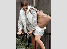 Eva Mendes legs it over a fence in heels and a short skirt