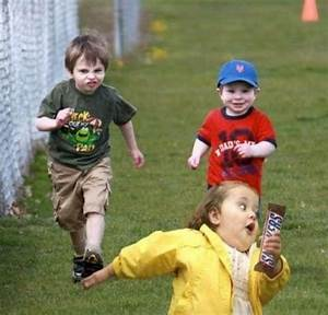 little girl running away from two boys with a snickers bar ...