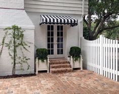 white colonial house exterior navy shutters striped awnings favorite places spaces
