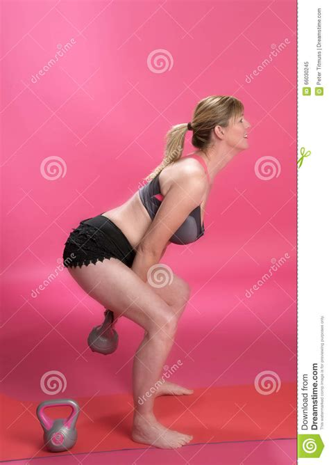 woman kettle using exercise bell knees bent preview sports