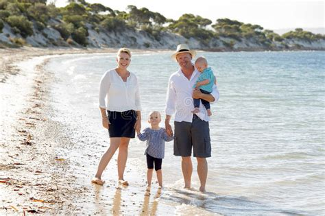 Young Happy Beautiful Family Walking Together On The Beach
