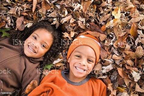 Kids Lying On Leaves Stock Photo - Download Image Now - iStock