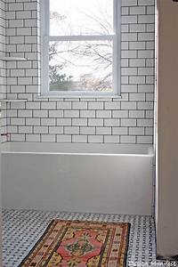 dark grout unites the white subway tile tub surround and With white bathroom tiles with black grout