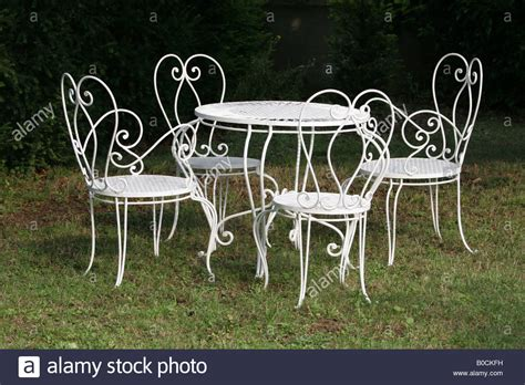 white wrought iron dining table and chairs in garden stock