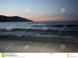 Dark blue sea waves over light sand with mountain and ...