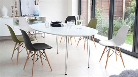 white extending dining table and eames style dining chairs