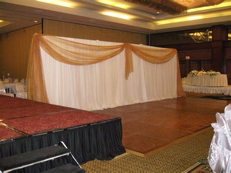 How Much Does Draping Cost For A Wedding - reception white ceremony gold backdrop draping