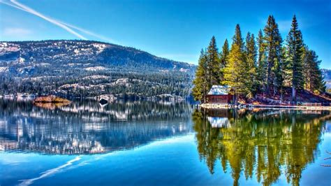 peaceful lake wooden house snow hills forest pine trees